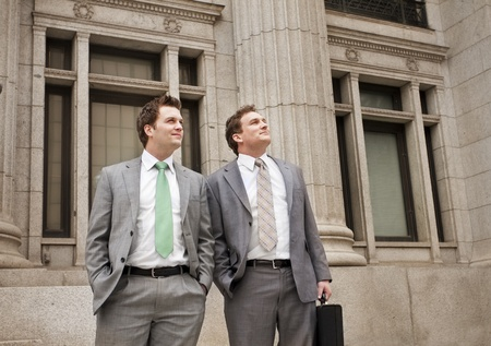 Optimistic Young Businessmen standing outside office building photo