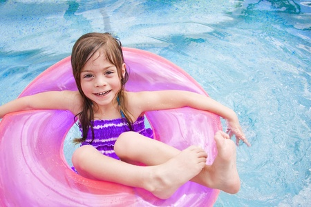 Child Happily playing in the swimming pool on vacation photo