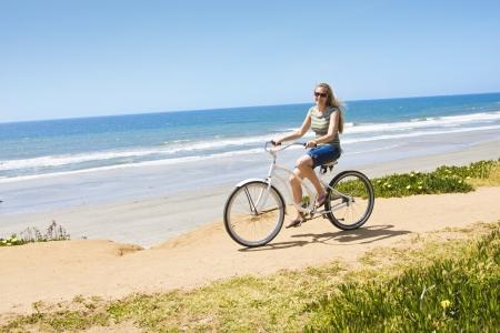 Vrouw op een fietstocht langs het strand Stockfoto