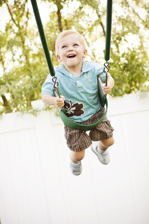 A little boy happily playing on the swings outdoors Stock Photo - 9785335
