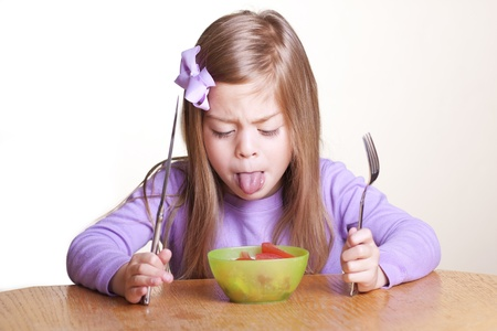 A cute little girl looks in disgust at her bowl of vegetables photo