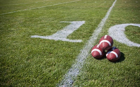 positioned: footballs positioned together on the sideline of a football field Stock Photo
