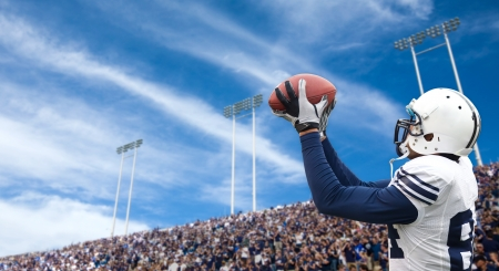 catch: Calciatore cattura un pass touchdown Archivio Fotografico