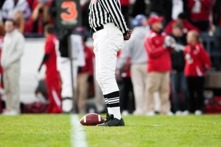 arbitro: Pelota descansando sobre la Yardline en un partido de f�tbol Foto de archivo