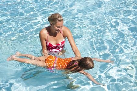 女の子が泳ぐことを学ぶ