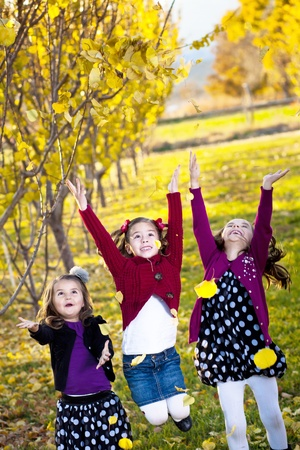 Children playing in the colorful fall leaves photo