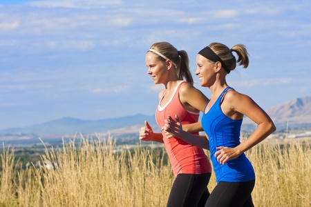 mid morning: Two beautiful middle-aged female joggers training for a marathon  Stock Photo