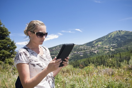 Woman using tablet computer outdoors photo