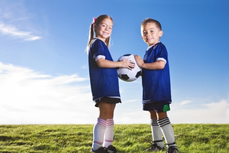 soccer ball on grass: Youth Soccer players smiling together on a grass field