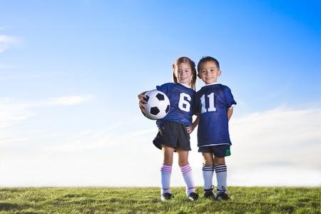 niños felices: Dos jugadores de fútbol juvenil lindos vestidos con sus uniformes de los equipos