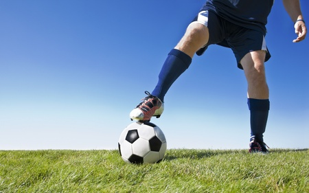 cleats: Soccer player kicking the ball during a game. - Lots of copy space