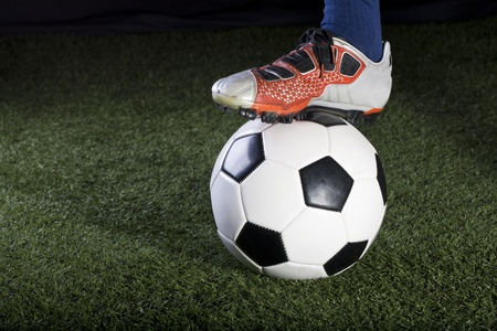cleat: Soccer ball resting on a grass field at night Stock Photo