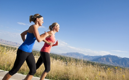 Side view of Two Female joggers running outdoors photo