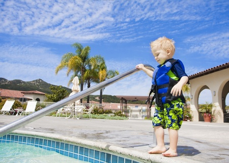 cautious: Little Boy Cautiously Stepping into Outdoor Pool in San Diego, California