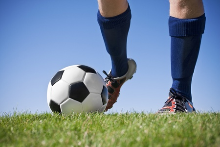 soccer cleats: Kicking the soccer ball (close, low angle view) Stock Photo
