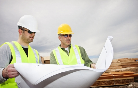 Two contractors reading construction plans at worksite