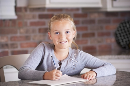 10 11 years: Cute little girl writing and studying in her notebook Stock Photo