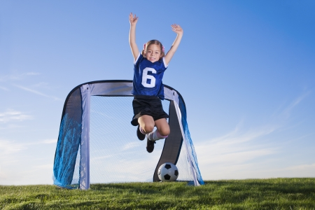 soccer uniforms: Young Girl playing soccer and scoring goal