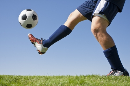 soccer cleats: Athlete Kicking a soccer ball on field