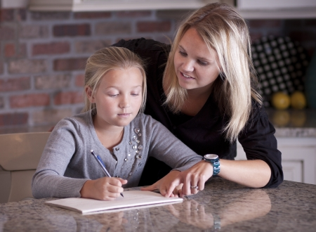 Mother helping her daughter with homework Stock Photo - 14295612