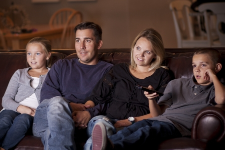 家族で一緒にテレビを見て 写真素材