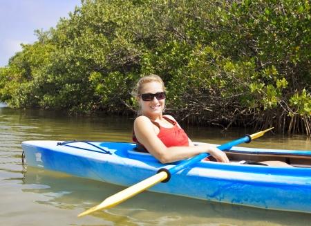 mangrove: Beautiful woman enjoying a kayak ride Stock Photo