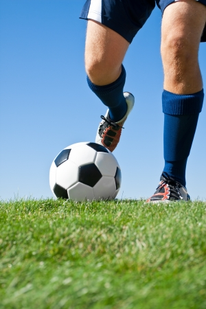 football cleats: Kicking the Ball low angle Stock Photo