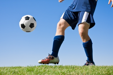 soccer cleats: Soccer Player Kicking the ball - low angle Stock Photo