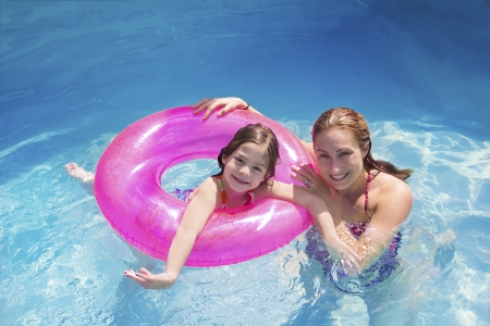 swimming to float: Family Summer Fun in the Swimming Pool Stock Photo