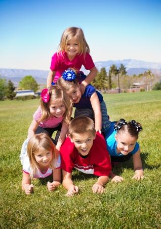 human pyramid: Cute Kids Building a Human Pyramid outdoors Stock Photo