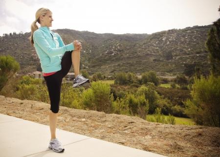魅力的な女性ランナーのトレーニング前にストレッチ