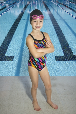 little girl swimsuit: Confident Young Swimmer standing by Swimming Pool