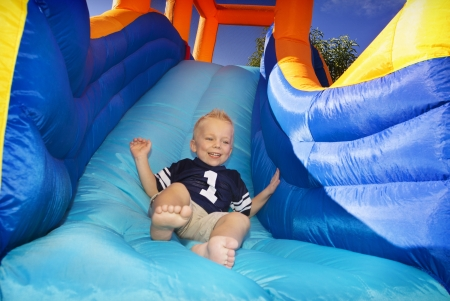 playgrounds: Boy sliding down an inflatable Side  Stock Photo