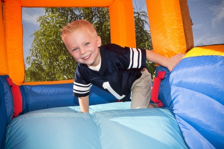kids birthday party: Boy playing on and inflatable Side