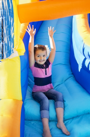 Little Girl sliding down an inflatable Slide photo