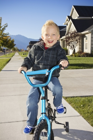 training wheels: Little boy learning to ride a bike with training wheels Stock Photo