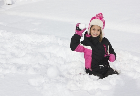 Little girl having a snowball fight photo