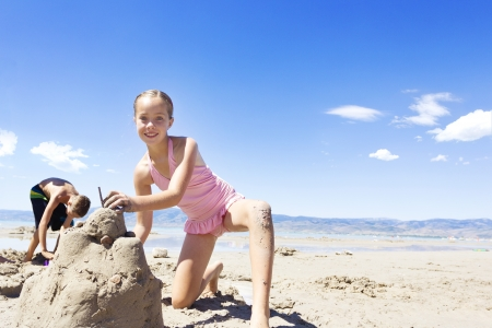 kids playing beach: Girl Building a Sand Castle at the Beach
