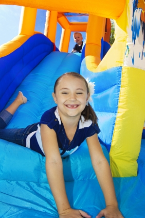 Kids playing on an inflatable slide bounce house Imagens