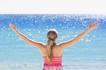 arm extended: Woman Enjoying the Sunshine at the beach Stock Photo
