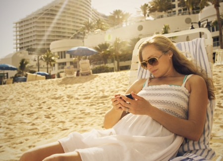 Woman Using her smartphone at the beach Banco de Imagens
