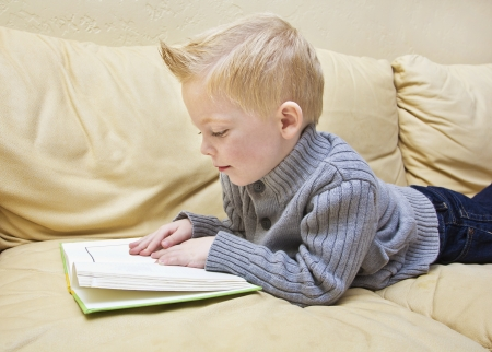 one story: Cute boy reading a book on the couch Stock Photo