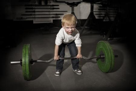 levantamiento de pesas: Decidido Boy joven que intenta levantar pesos pesados
