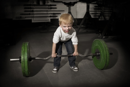 strong boy: Determined Young Boy trying to lift Heavy weights Stock Photo