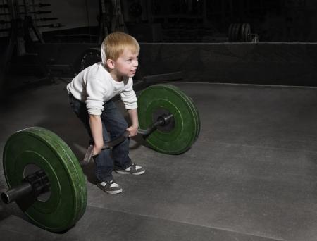 Déterminé Jeune garçon essayant de soulever des poids lourds Banque d'images