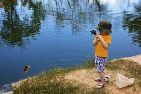 angling: Little Boy Catching a Fish
