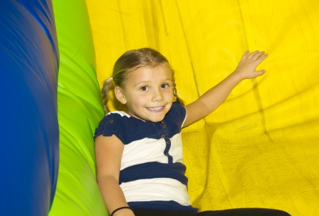 bounce: Cute little Girl playing on inflatable Side