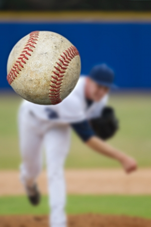 Baseball Pitcher Throwing focus on Ball photo