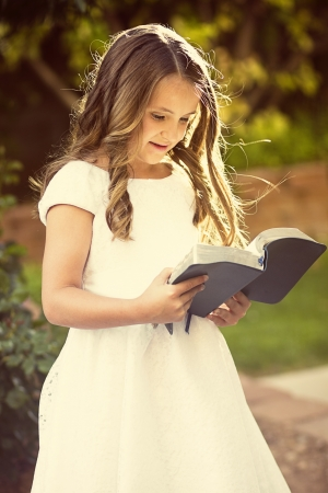 sunday school: Cute little girl reading the Bible