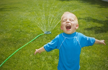 summer fun: Young boy playing in the sprinklers outdoors Stock Photo